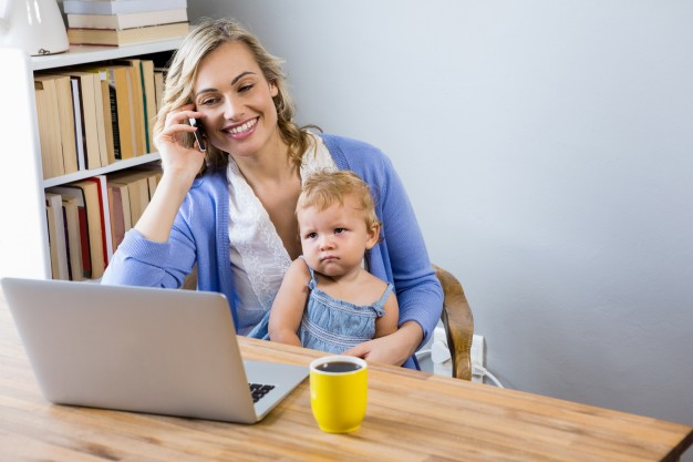 mother-talking-on-mobile-phone-with-baby-on-her-lap_1170-100